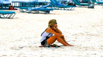 Frau sitzt alleine am Strand