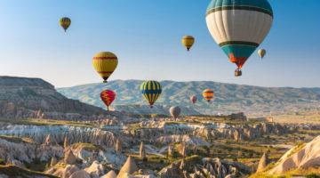 Ballonfahrt über ein Gebirge bei Sonnenschein