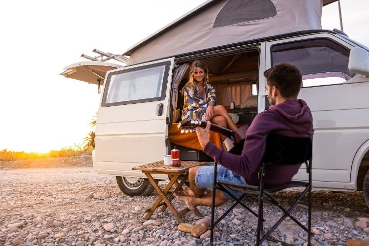 Paar sitzt vor ihrem Camper