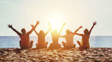 Freunde am Strand bei Sonnenuntergang