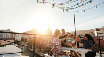 Menschen sitzen auf dem Balkon mit Getränken