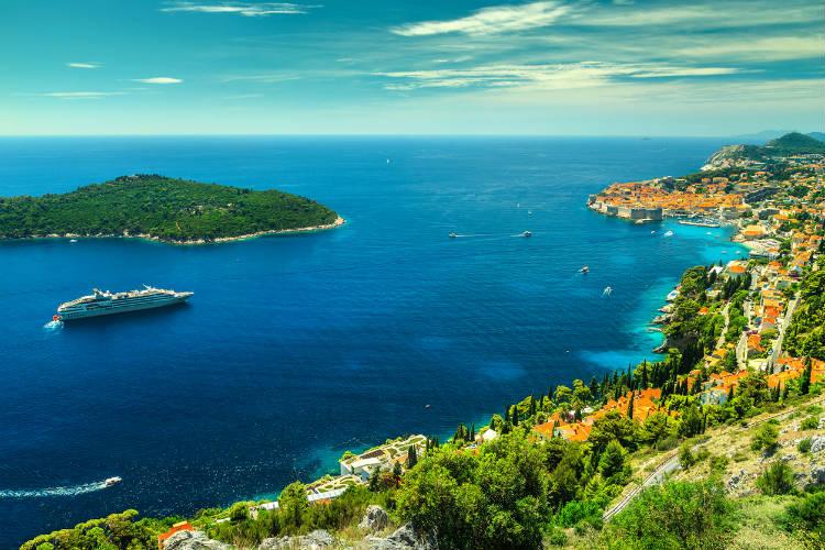 Grünes Küstenbild mit blauem Meer und Kreuzfahrtschiff in der Ferne