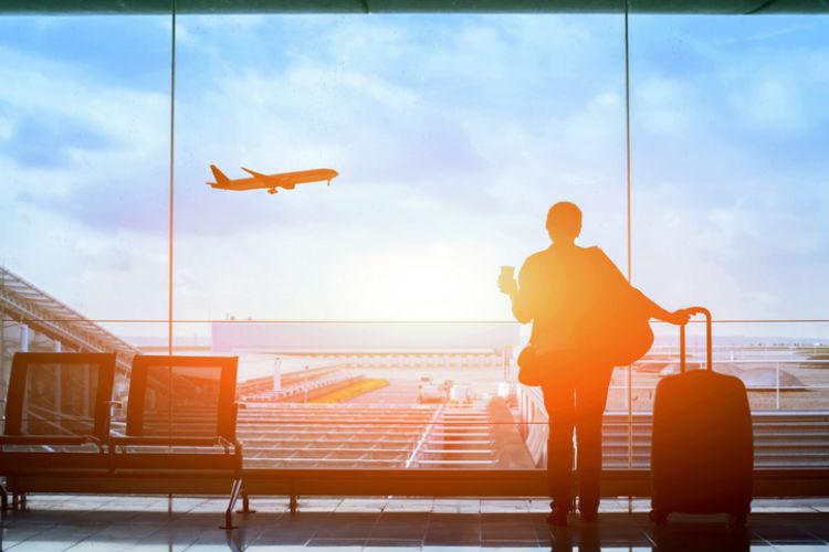 Frau steht im Flughafenterminal und beobachtet ein Flugzeug beim Abheben