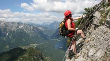 Person die an Felswand klettert