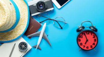 Reisepass und weitere Reiseaccessoires die neben einer Uhr auf einem Tisch liegen