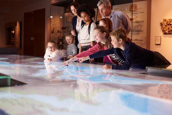 Kinder und Erwachsene erkunden gemeinsam eine digitale Landkarte