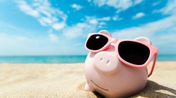 Sparschwein, das am Strand steht mit Sonnenbrille