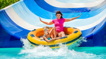 Kind mit Mutter auf Wasserrutsche - Campingplatz mit Schwimmbad