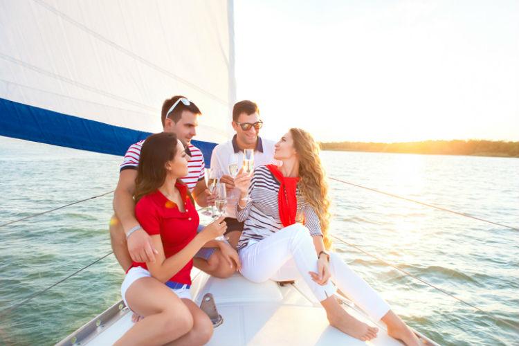 Yachturlaub - 4 Freunde sitzen an Deck einer Segelyacht