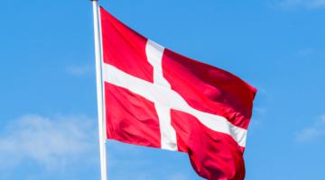 Eine Flagge von Dänemark vor blauem Himmel