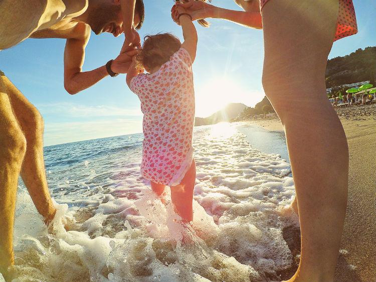 Kleinkind am Strand mit seinen Eltern