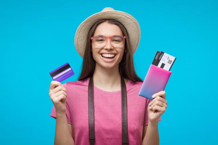Glückliche Frau die EC Karte und Reisepass in der Hand hält