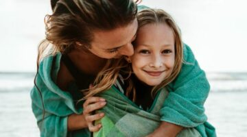 Frau mti Tochter im Handtuch umhüllt