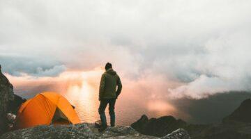 Mann steht neben Zelt auf dem Berg und schaut Sonnenuntergang an