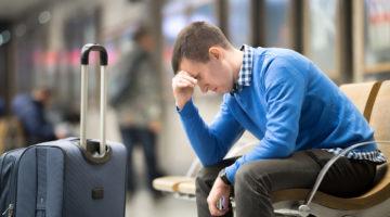 Junger, müder Mann sitzt mit Gepäck am Flughafen