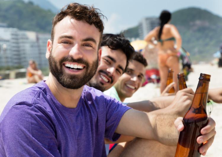 Jungs sitzen am Strand und trinken Bier