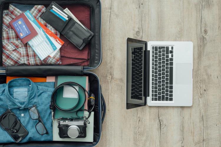 Offener Koffer und Laptop von oben auf Holzboden