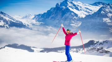 Frau steht auf Ski am Berggipfel und freut sich