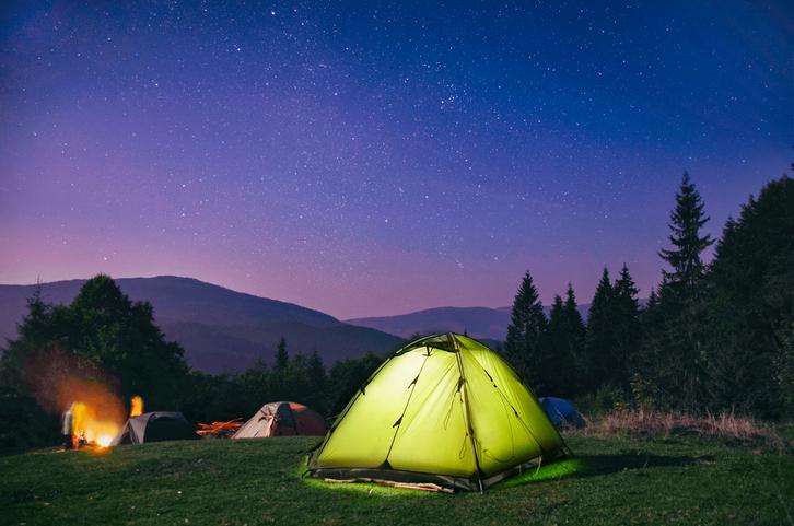 Zelt auf einer Wiese unter Sternenhimmel