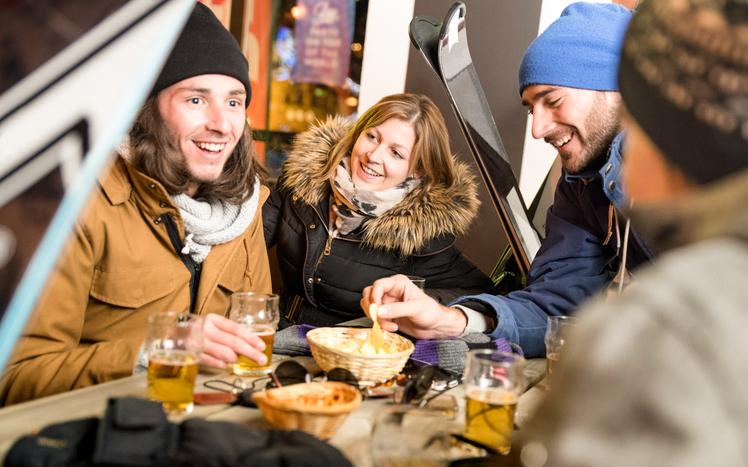 Feiernde Menschen sitzen beim Après-Ski