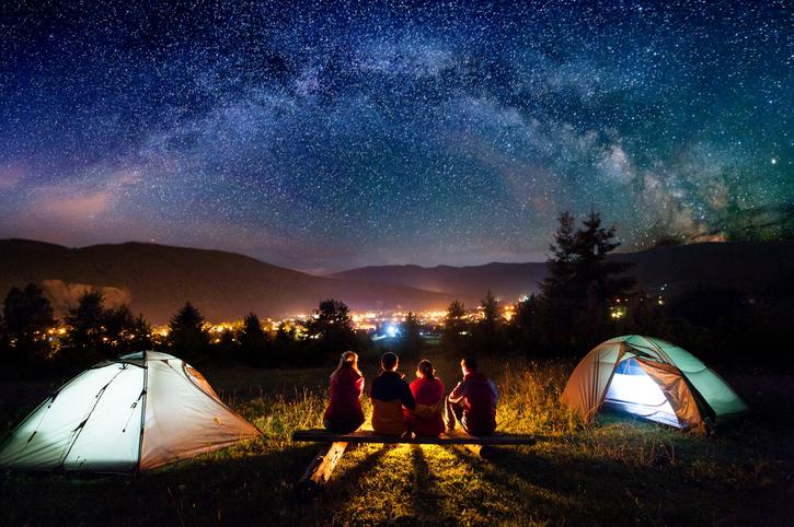 Zwei Zelte und Camper unter Nachthimmel