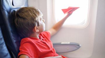 Kind mit Papierflugzeug im Flugzeug