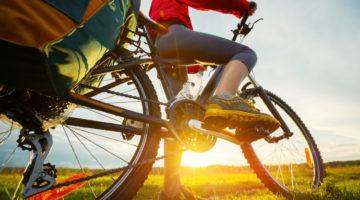 Fahrradfahrerin mit bepacktem Trekkingrad im Sonnenuntergang