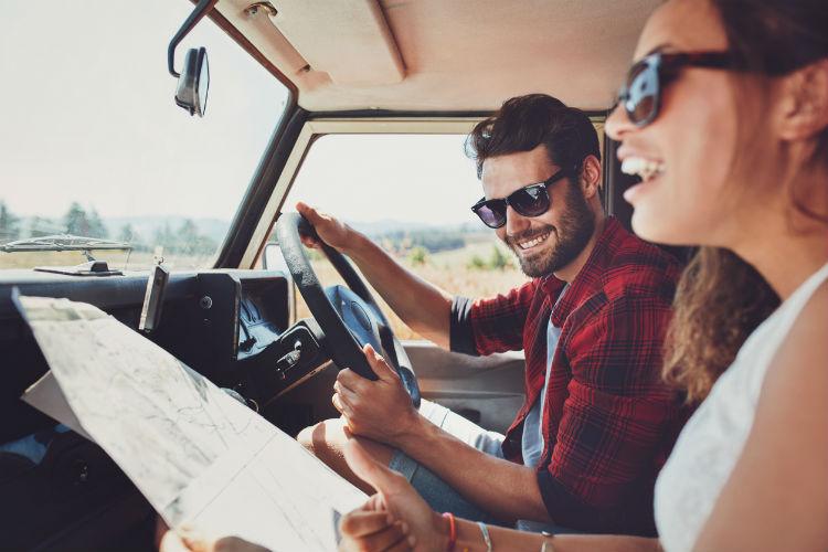 Junges Paar im Auto mit Landkarte