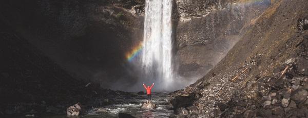 mann steht vor wasserfall mit regenbogen